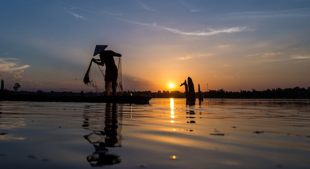 Silueta del pescador de redes de pesca en el barco.