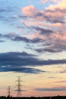 Silueta de poste de alto voltaje y fondo de nubes.