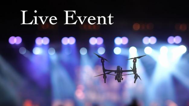 Silueta de primer plano de drone volando para tomar video de multitud de conciertos