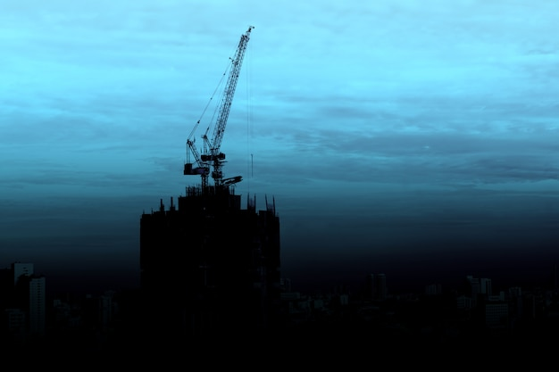 Silueta de rascacielos en construcción con grúa en el fondo del atardecer crepuscular