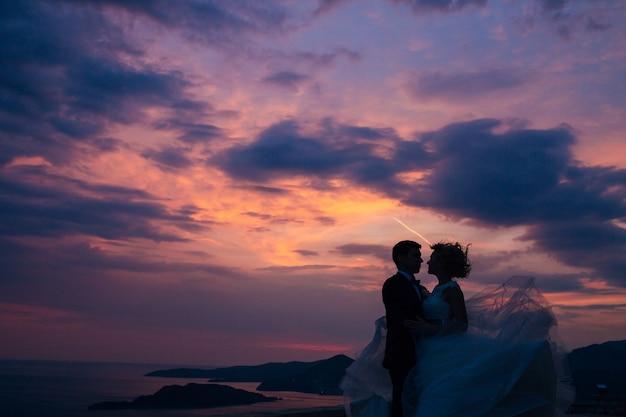 Silueta de los recién casados contra el cielo en la boda al atardecer