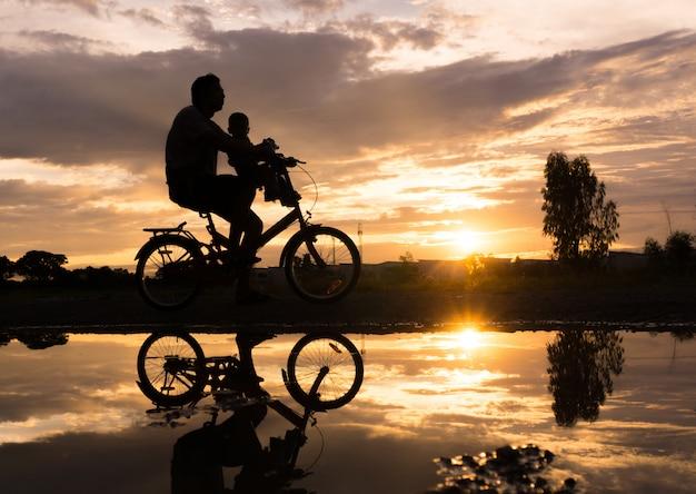 Silueta de reflexión del padre con su niño en bicicleta contra la puesta de sol.