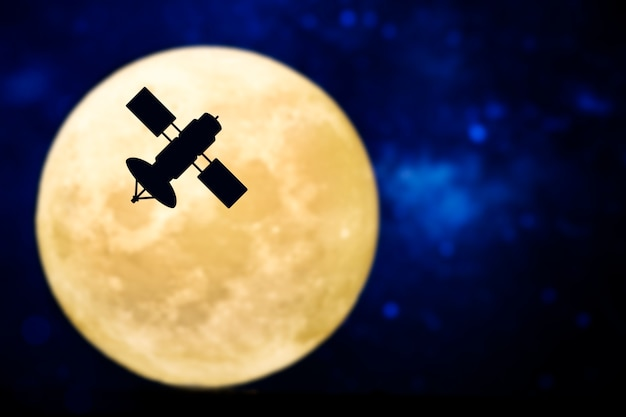 Silueta de satélite sobre luna llena