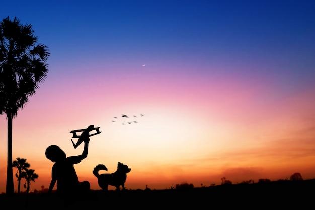Silueta de sueños de niños como piloto de pie y sosteniendo papel de avión en puesta de sol