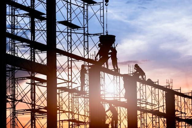 Silueta de trabajador construcción edificio de fundición de hormigón sobre andamios.