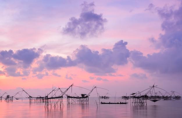 Silueta de la trampa de la red de pesca en el paisaje marino del amanecer en phatthalung, tailandia
