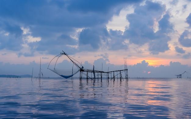 Silueta de la trampa de la red de pesca en el paisaje marino de la salida del sol en phatthalung, tailandia