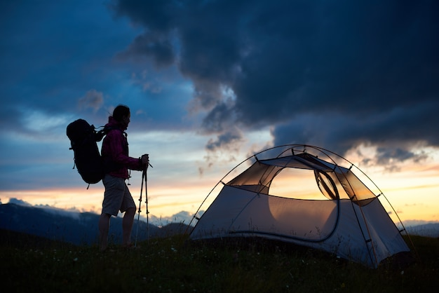 Silueta de turista cerca de la tienda con mochila sobre sus hombros y bastones en las manos disfrutando de la vista del atardecer sobre las montañas. concepto de viaje y estilo de vida activo.
