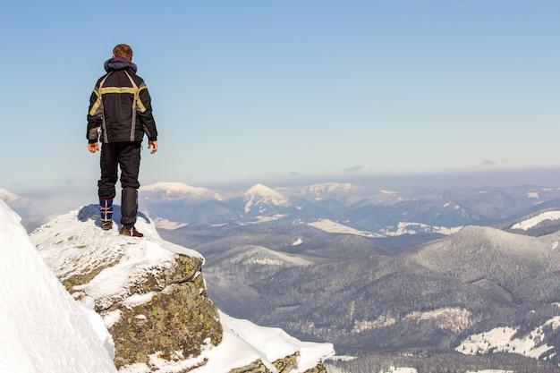 Silueta de turista solo parado en la cima de la montaña nevada disfrutando de vista