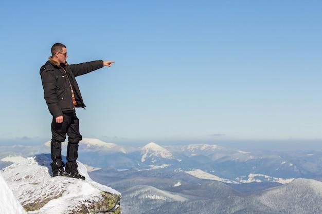 Silueta del turista solo que se coloca en la cima de la montaña nevada que disfruta de la vista y del logro en día de invierno soleado brillante.