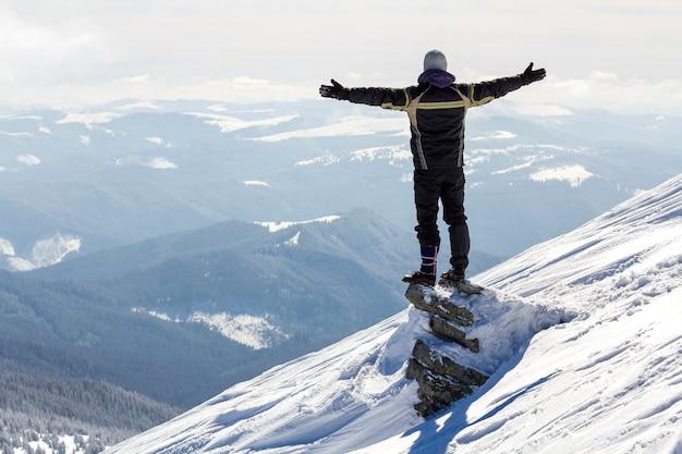 La silueta del turista solo que se coloca en la cima nevada de la montaña en pose del ganador con las manos levantadas que disfruta de la vista y del logro en día de invierno soleado brillante. aventura, actividades al aire libre, estilo de vida saludable.