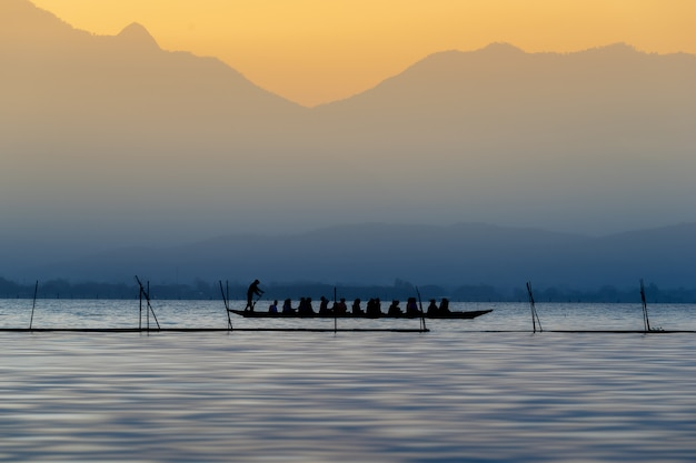 Silueta de turistas en el barco de madera en el lago phayao, tailandia.