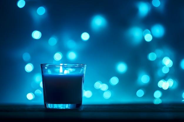 Silueta de vela encendida con luces doradas borrosas