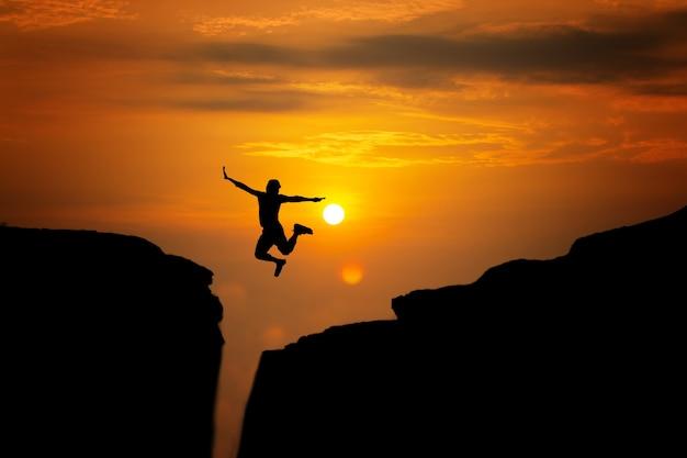 Silueta de viaje de hombre saltar para logros exitosos y celebrar el éxito con salida del sol