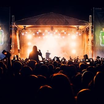 Siluetas de cabezas y manos de una multitud de fanáticos en un concierto en vivo