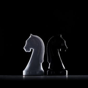 Siluetas de caballeros de ajedrez blancos y negros aislados en negro, concepto de negocio