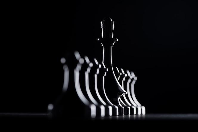 Siluetas de peones de ajedrez y reina aislados en negro, concepto de negocio
