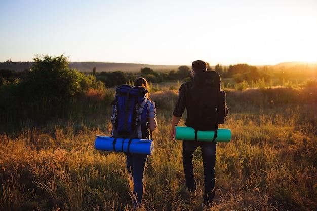 Siluetas de dos excursionistas con mochilas caminando al atardecer.