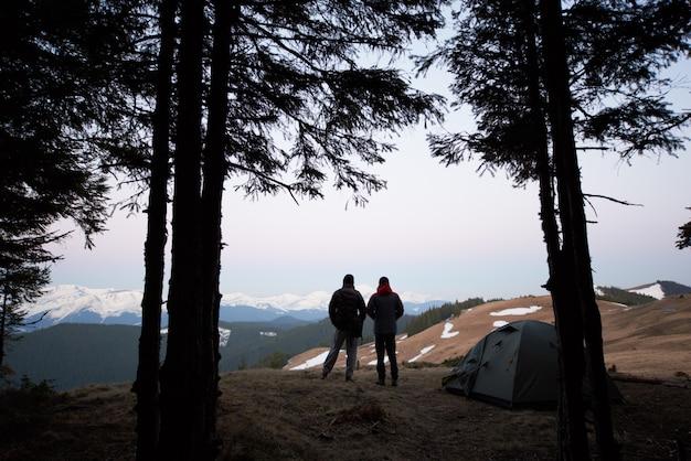 Siluetas de dos hombres de pie cerca de su tienda de campaña en la cima de la montaña mientras acampan juntos
