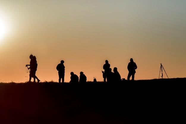 Siluetas de excursionistas con mochilas disfrutando de la vista del atardecer desde la cima de una montaña