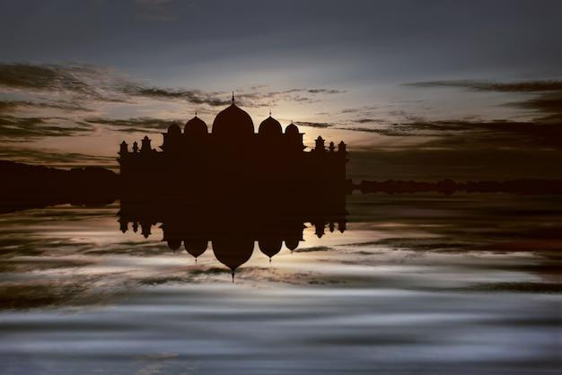 Siluetas de gran mezquita con reflejo en el agua.