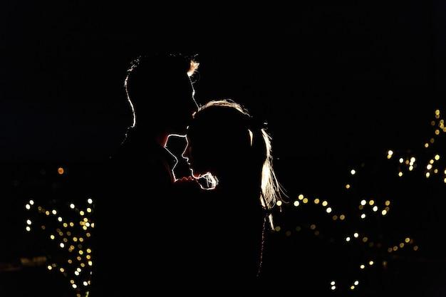 Siluetas de una hermosa joven pareja de pie en la azotea en la noche