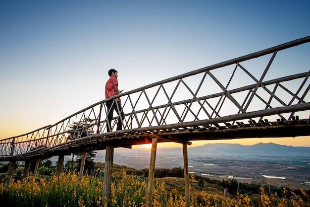 Siluetas de hombre asiático de pie en el puente de bambú en ban doi sa-ngo chiangsaen, provincia de chiang rai, tailandia.