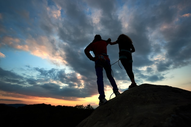Las siluetas del hombre y la mujer miran la puesta de sol en la cima de la roca. los excursionistas se juntan en el cielo dramático al atardecer. vista trasera.
