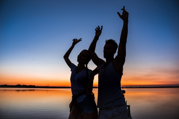 Siluetas de joven pareja hermosa descansando regocijo al amanecer cerca del lago