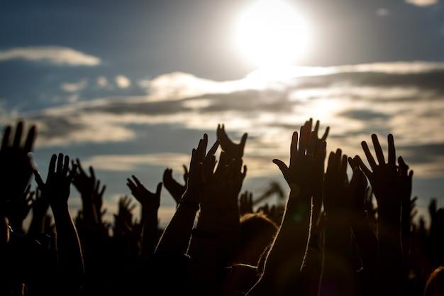 Siluetas de manos de personas con manos levantadas