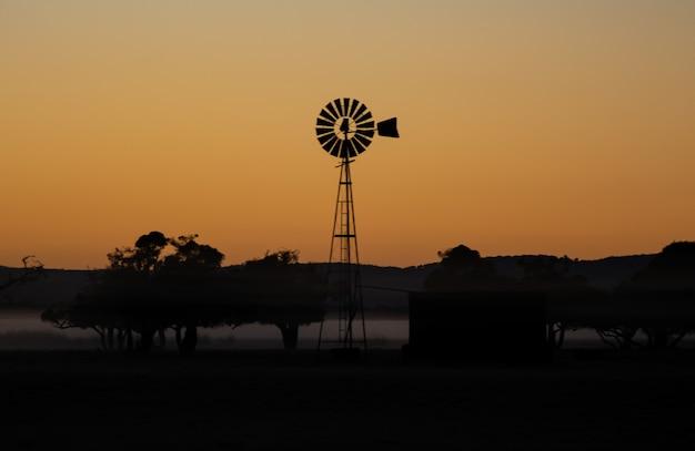 Siluetas de un molino de viento y árboles durante una increíble puesta de sol en la noche