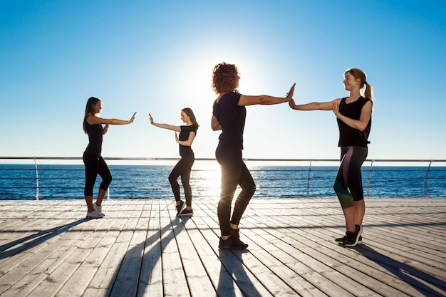 Siluetas de mujeres deportivas bailando zumba cerca del mar al amanecer