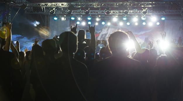 Siluetas de multitud en concierto cerca del escenario
