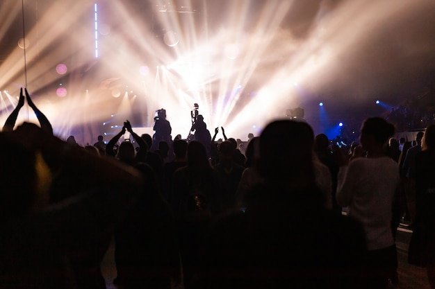 Siluetas de una multitud de conciertos y un camarógrafo en el contexto de rayos brillantes y coloridos en el escenario. la cámara con el operador está en la plataforma alta.