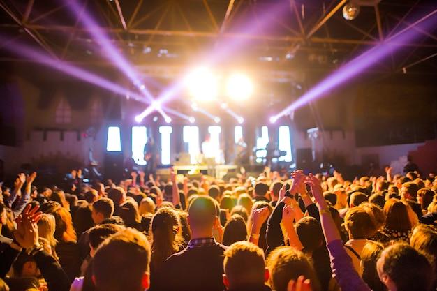 Las siluetas de la multitud de conciertos frente a las luces del escenario brillante. concierto de una banda de rock abstracto