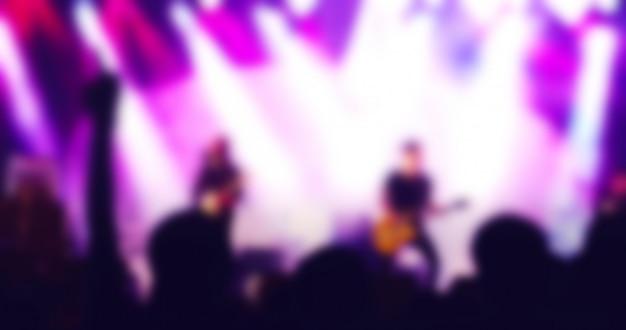 Siluetas de multitud de conciertos en la vista trasera de la multitud del festival levantando sus manos sobre luces brillantes del escenario