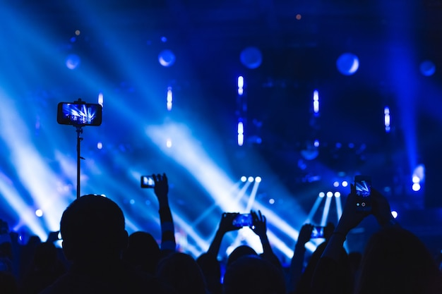 Siluetas de multitudes de espectadores en un concierto con smartphones en sus manos. la escena está bellamente iluminada por focos.