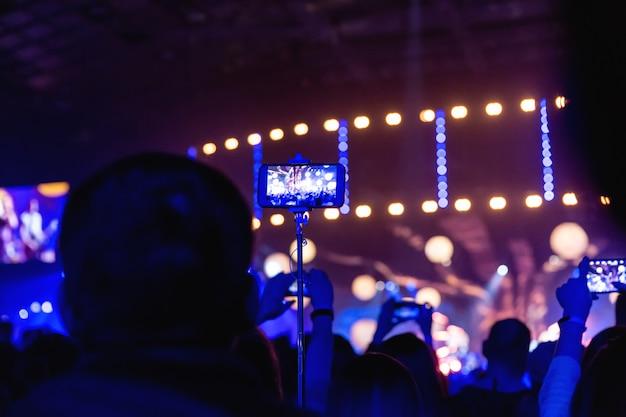 Siluetas de multitudes de espectadores en un concierto con teléfonos inteligentes en sus manos. la escena está bellamente iluminada por focos.