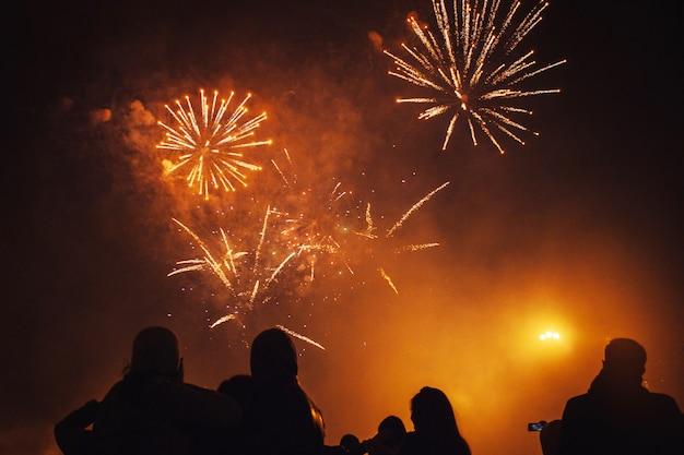 Siluetas de multitudes de personas que observan los fuegos artificiales. celebra las vacaciones en la plaza. gran diversión