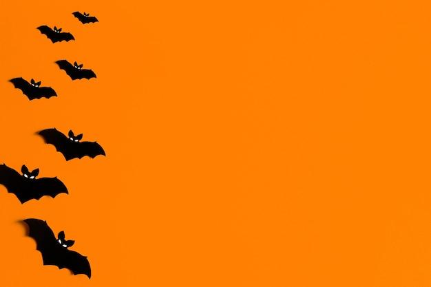 Siluetas de murciélagos de papel negro sobre un fondo naranja para halloween