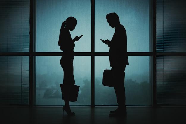 Siluetas oscuras de hombre y mujer en traje de negocios de pie junto a la ventana por la noche con teléfonos inteligentes