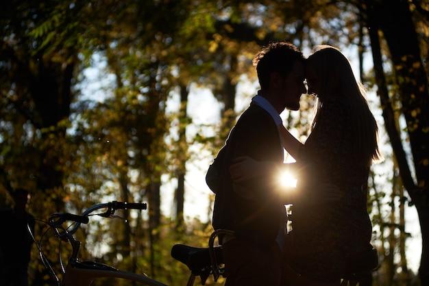 Siluetas de pareja romántica en el parque otoño