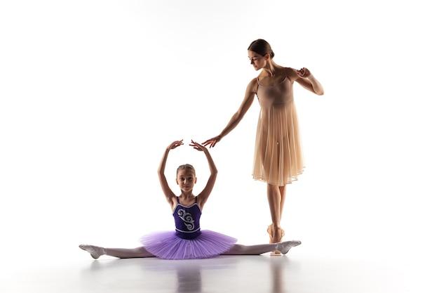 Las siluetas de la pequeña bailarina y profesora de ballet clásico personal en el estudio de danza bailando sobre un fondo blanco.
