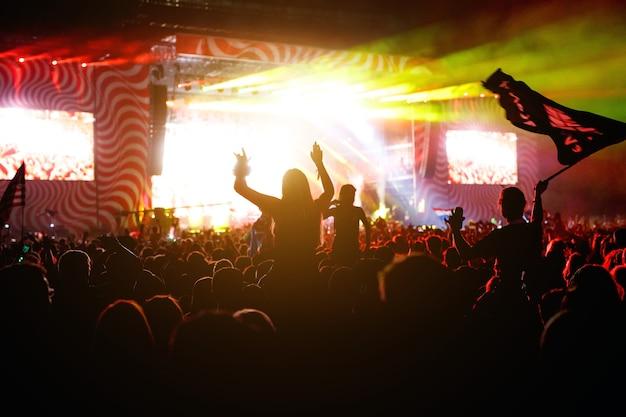Siluetas de personas en concierto multitud frente a las luces del escenario brillante