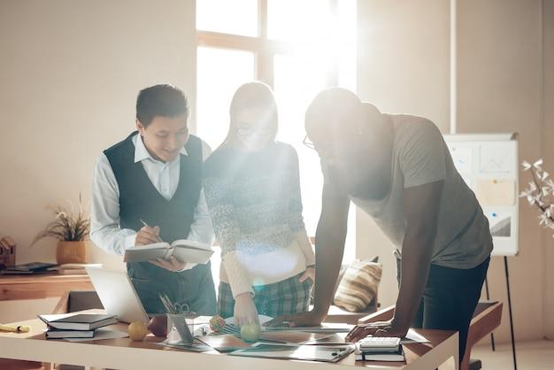 Siluetas de personas diseñadores de luz solar en la oficina.