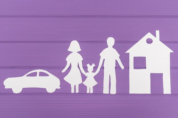 Las siluetas recortadas de papel de hombre y mujer con una niña cerca de la casa y el automóvil