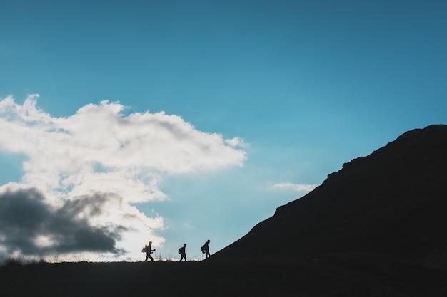 Siluetas de viajeros-turistas subiendo cuesta arriba contra el fondo de nubes y cielo azul