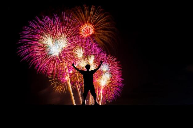 Siluetee al hombre acertado en el pico, exhibición colorida hermosa de los fuegos artificiales en la playa del mar.