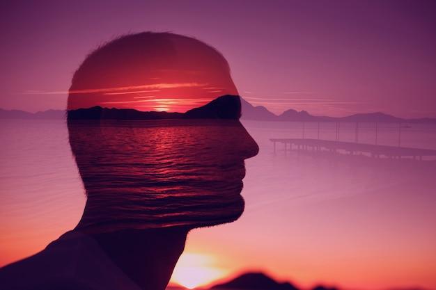 Siluetee al hombre joven encendido de la puesta del sol sobre el mar.