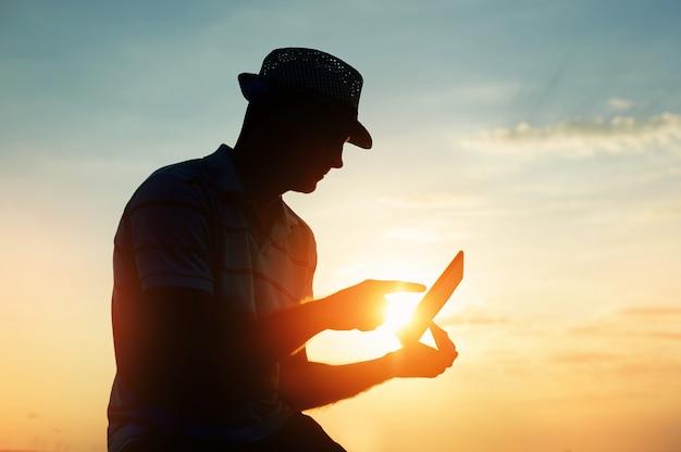 Siluetee al hombre que trabaja en su computadora portátil en la playa durante puesta del sol